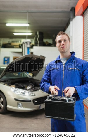 Portrait of confident auto mechanic with car battery in workshop - stock photo