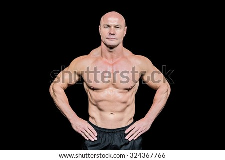 Portrait of confident bald man with hands on hip against black background - stock photo