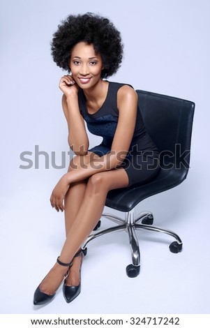 Portrait of confident black african business woman smiling and sitting on executive chair in studio, isolated on grey background - stock photo
