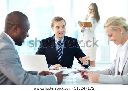 Portrait of confident boss explaining strategy to his partners at meeting - stock photo