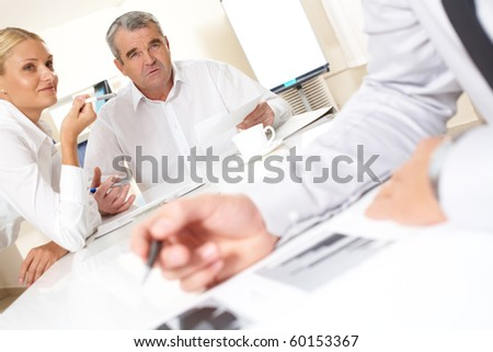 Portrait of confident boss looking at one of workers while talking to him - stock photo