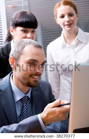 Portrait of confident boss pointing at laptop screen during briefing
