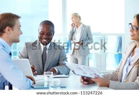 Portrait of confident boss smiling while his partners interacting at meeting