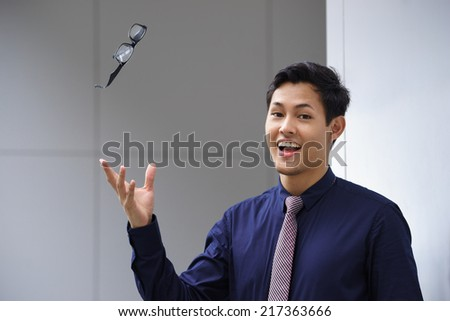 Portrait of confident businesman with eyesight myopia problem, throwing away his eyeglasses and looking at camera smiling - stock photo