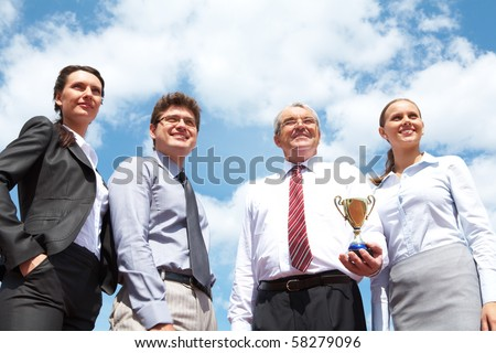 Portrait of confident business group on background of cloudy sky - stock photo