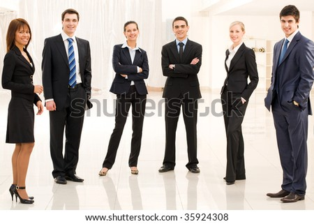 Portrait of confident business group standing in semi-circle and looking at camera - stock photo