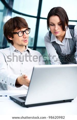 Portrait of confident business man explaining a project to colleague at the office - stock photo