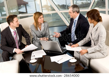 Portrait of confident business partners communicating in office at meeting - stock photo