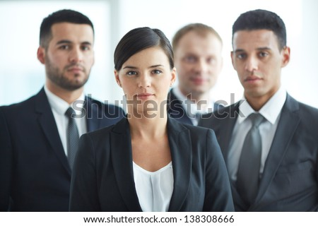 Portrait of confident business partners looking at camera with female leader in front - stock photo
