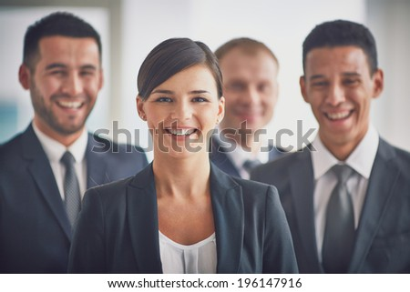 Portrait of confident business partners looking at camera, young smiling woman on foreground - stock photo