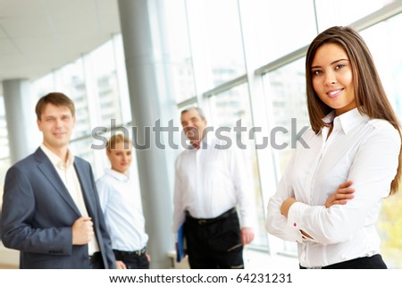 Portrait of confident business people looking at camera with pretty brunette in front