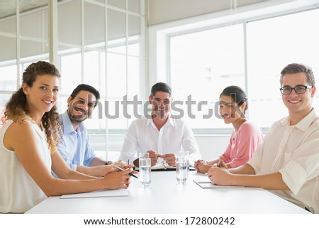 Portrait of confident business people sitting at conference table in office - stock photo