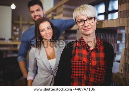 Portrait of confident business people standing by rack in creative office - stock photo