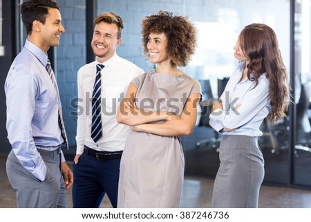 Portrait of confident business team standing in office with their hands crossed - stock photo