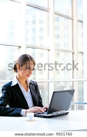 Portrait of confident business woman sitting at the table and typing a document on the laptop