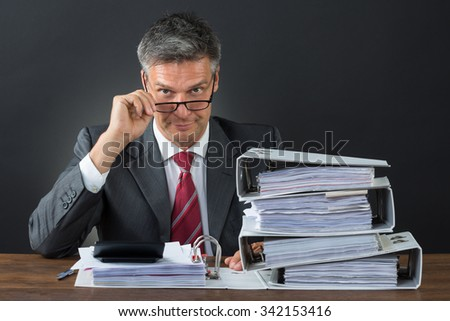Portrait of confident businessman checking invoice at desk against gray background