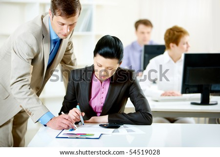 Portrait of confident businessman consulting pretty employee in office - stock photo