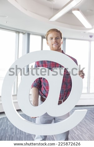 Portrait of confident businessman holding at sign in creative office - stock photo