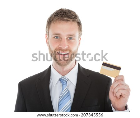 Portrait of confident businessman holding credit card over white background - stock photo