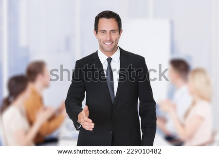Portrait of confident businessman offering handshake while colleagues applauding in background at office - stock photo