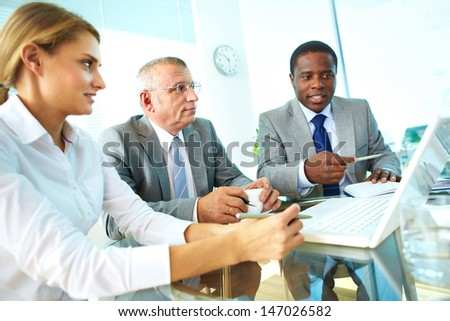 Portrait of confident businessman pointing at laptop screen while explaining something to his colleagues