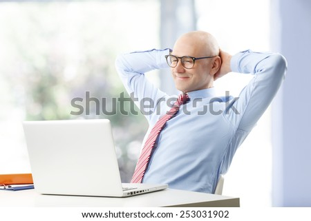 Portrait of confident businessman sitting at desk while relaxing at office.