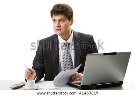 Portrait of confident businessman sitting at workplace and looking aside