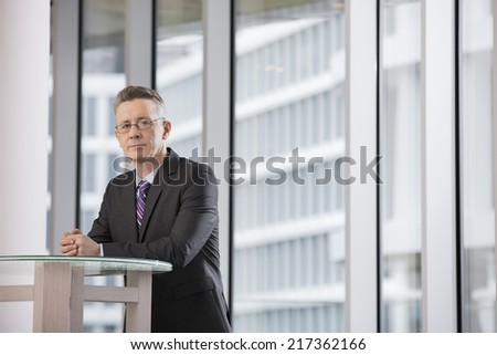 Portrait of confident businessman standing in office - stock photo