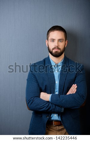 Portrait of confident businessman standing isolated over blue background - stock photo