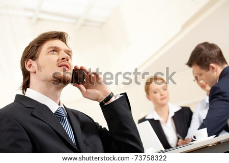 Portrait of confident businessman talking by cellphone with working team on background - stock photo