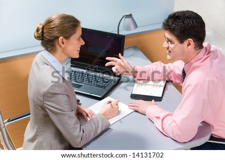 Portrait of confident businessman talking to smiling woman while she looking at him