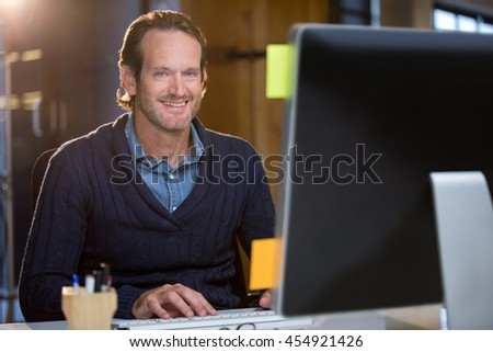 Portrait of confident businessman using computer at desk in office