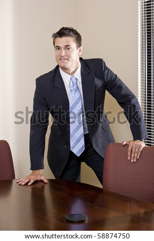 Portrait of confident businessman wearing suit in boardroom