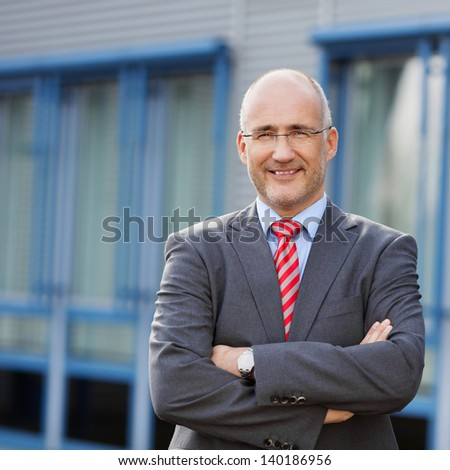 Portrait of confident businessman with arms crossed standing against building - stock photo