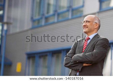 Portrait of confident businessman with arms crossed standing against office - stock photo