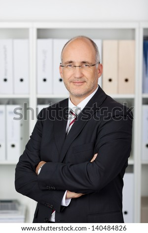 Portrait of confident businessman with arms crossed standing in office - stock photo