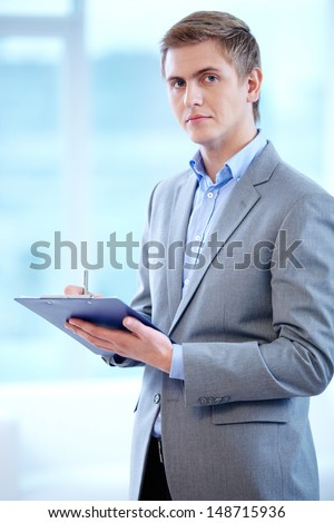 Portrait of confident businessman with clipboard looking at camera while making notes