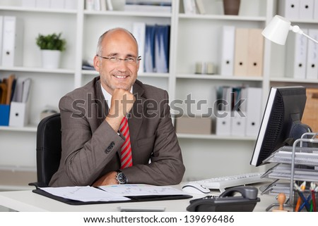 Portrait of confident businessman with hand on chin sitting at office desk - stock photo