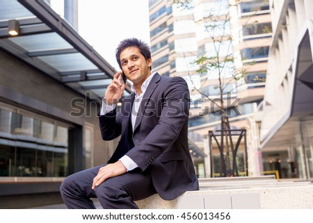 Portrait of confident businessman with mobile phone outdoors