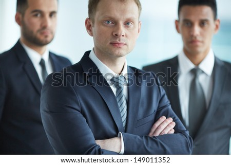 Portrait of confident businessmen looking at camera with young leader in front - stock photo