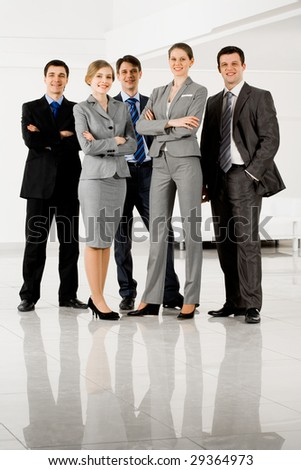 Portrait of confident businesspeople in smart suits standing on the floor - stock photo