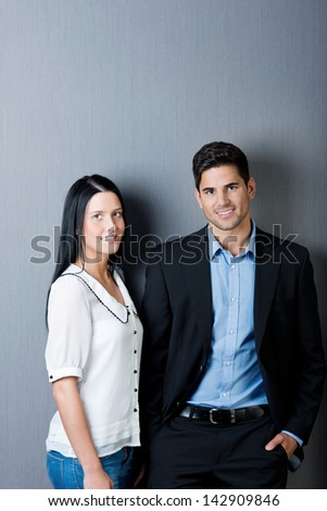 Portrait of confident businesspeople standing against blue wall - stock photo