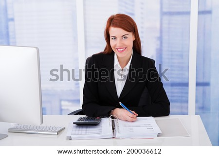 Portrait of confident businesswoman calculating tax at office tax - stock photo