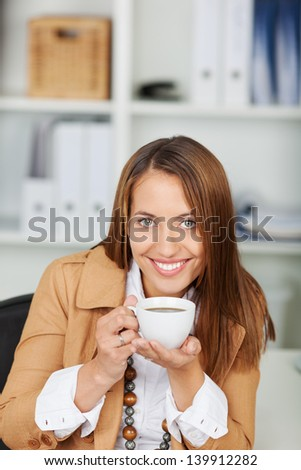 Portrait of confident businesswoman holding cup of coffee at office desk - stock photo