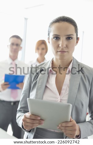 Portrait of confident businesswoman holding digital tablet with colleagues in background at office - stock photo
