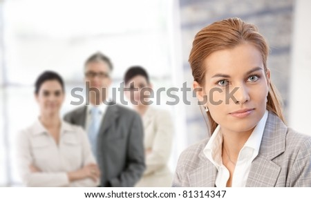 Portrait of confident businesswoman in closeup, with colleagues in background.? - stock photo