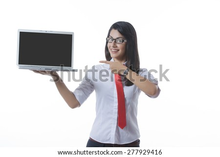 Portrait of confident businesswoman pointing at laptop over white background - stock photo