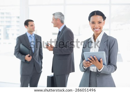 Portrait of confident businesswoman using a tablet with colleagues behind in office - stock photo