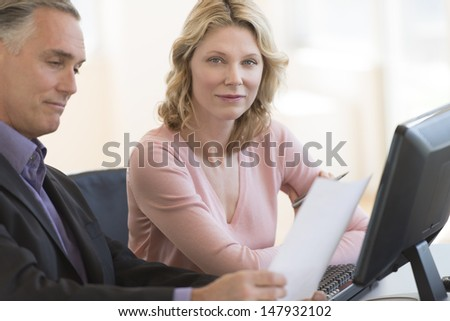 Portrait of confident businesswoman with colleague reading document at desk in office - stock photo