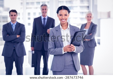 Portrait of confident businesswoman with colleagues behind in office - stock photo